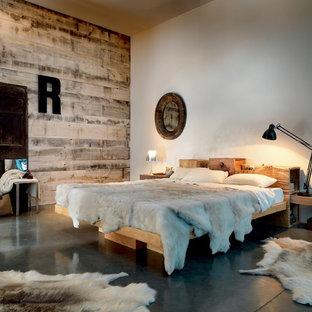 Immagine di una camera matrimoniale stile rurale con pareti bianche e pavimento in cemento