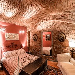 Immagine di una camera da letto mediterranea di medie dimensioni con pareti rosse e pavimento in mattoni