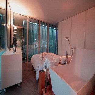 Modelo de dormitorio principal, contemporáneo, con paredes grises y suelo de cemento