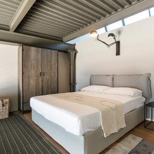 Foto de dormitorio tipo loft, industrial, pequeño, con paredes beige, suelo de madera en tonos medios y suelo multicolor
