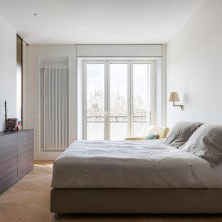 Foto di una camera matrimoniale moderna con pareti bianche, parquet chiaro e pavimento beige