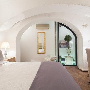 Exemple d'une grande chambre parentale nature avec un mur blanc et un sol en brique.