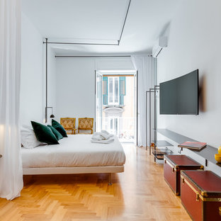 Esempio di una camera da letto design con pareti bianche, pavimento in legno massello medio e pavimento marrone