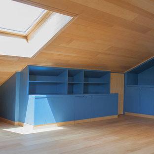 Imagen de dormitorio tipo loft, minimalista, de tamaño medio, con suelo de madera pintada, chimenea tradicional y marco de chimenea de madera