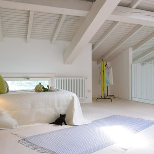 This is an example of a mediterranean loft-style bedroom in Milan with white walls, light hardwood floors and beige floor.