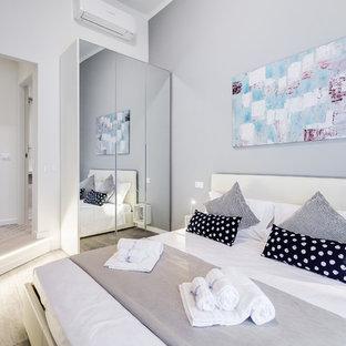 Esempio di una camera da letto contemporanea con pareti bianche, parquet chiaro e pavimento beige