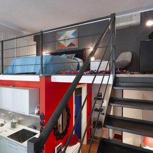 Expansive industrial loft-style bedroom in Turin with grey walls, dark hardwood floors and brown floor.