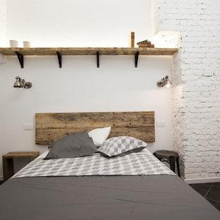 Esempio di una camera matrimoniale industriale di medie dimensioni con pareti bianche, pavimento in gres porcellanato e pavimento nero