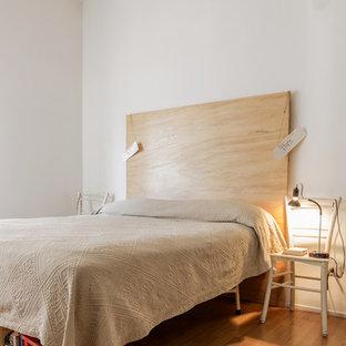 Esempio di una piccola camera da letto contemporanea con pareti bianche e parquet chiaro