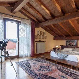 Esempio di una camera da letto stile loft mediterranea con pareti beige, pavimento in legno massello medio e pavimento marrone