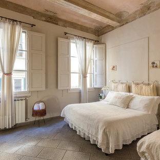 Immagine di una camera da letto mediterranea con pareti bianche e pavimento grigio
