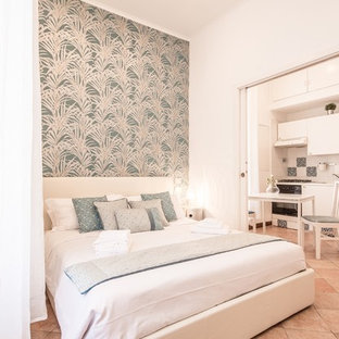 Design ideas for a small mediterranean master bedroom in Rome with white walls, terra-cotta floors and red floor.