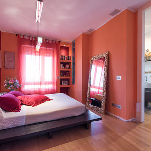 Example of a mid-sized trendy master light wood floor bedroom design in Milan with red walls