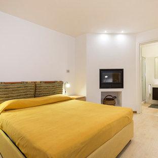 Стильный дизайн: маленькая гостевая спальня в стиле рустика с белыми стенами, паркетным полом среднего тона, горизонтальным камином, фасадом камина из металла и бежевым полом - последний тренд