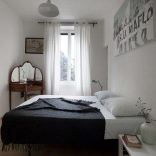 Esempio di una camera matrimoniale scandinava di medie dimensioni con pareti bianche, parquet chiaro e pavimento marrone