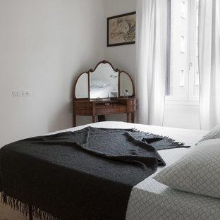 Diseño de dormitorio principal, escandinavo, de tamaño medio, con paredes blancas, suelo de madera clara, chimenea de esquina y suelo marrón