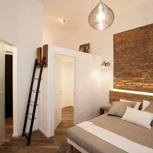 Idee per una camera matrimoniale industriale di medie dimensioni con pareti bianche, pavimento in gres porcellanato e pavimento marrone