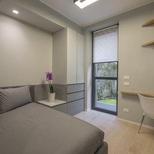 Esempio di una piccola camera degli ospiti moderna con pareti grigie, parquet chiaro e pavimento giallo