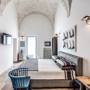 Foto di una camera da letto mediterranea con pareti bianche e pavimento grigio