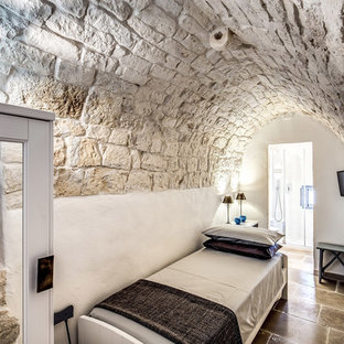 This is an example of a mediterranean guest bedroom in Rome with white walls and brown floor.