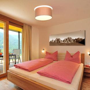 Immagine di una camera matrimoniale design di medie dimensioni con pareti bianche, pavimento in legno massello medio e nessun camino