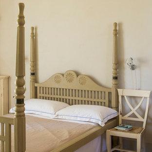 Immagine di una grande camera degli ospiti mediterranea con pareti beige, pavimento in pietra calcarea, camino classico, cornice del camino in legno e pavimento beige