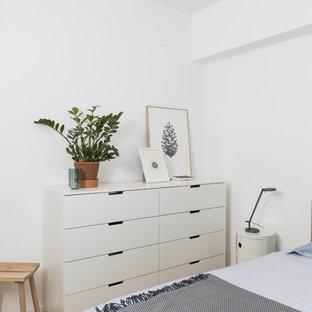 Immagine di una camera degli ospiti scandinava con pareti bianche, pavimento in legno massello medio e pavimento beige