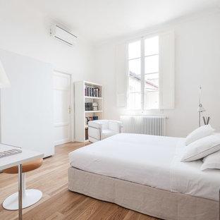 Ispirazione per una camera da letto design con pareti bianche, pavimento in legno massello medio e pavimento marrone