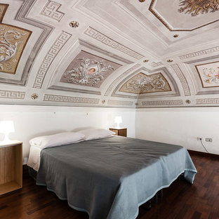 Immagine di una camera da letto mediterranea con pareti bianche, parquet scuro e pavimento marrone