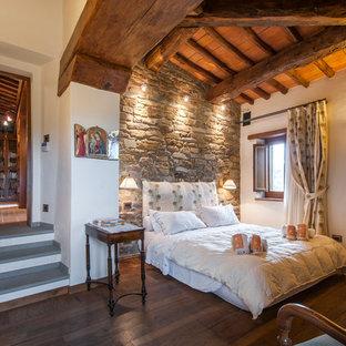 Esempio di una camera degli ospiti mediterranea con pareti bianche, parquet scuro e pavimento marrone