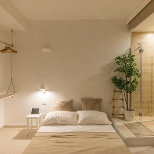 Design ideas for a mid-sized mediterranean loft-style bedroom in Other with white walls, porcelain floors, no fireplace and beige floor.