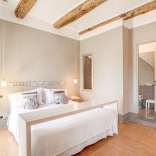 Esempio di una camera matrimoniale country di medie dimensioni con pareti beige e pavimento con piastrelle in ceramica