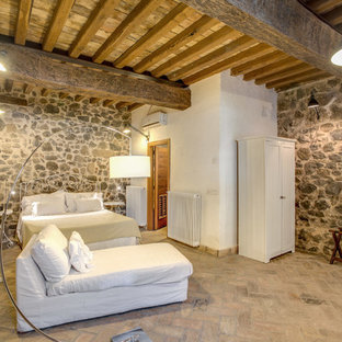 Expansive country master bedroom in Rome with brick floors.