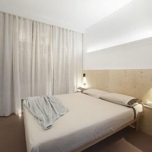 Ejemplo de dormitorio principal, moderno, pequeño, con paredes blancas, suelo de cemento y suelo rojo