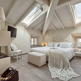 Foto på ett mellanstort funkis huvudsovrum, med vita väggar, ljust trägolv, en dubbelsidig öppen spis, en spiselkrans i gips och grått golv