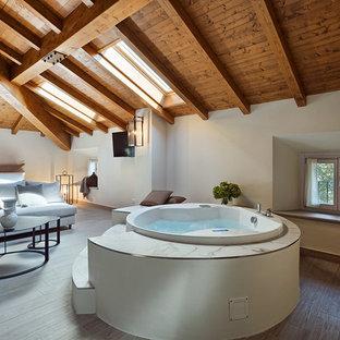 Свежая идея для дизайна: большая хозяйская спальня в современном стиле с белыми стенами, светлым паркетным полом, горизонтальным камином, фасадом камина из штукатурки и бежевым полом - отличное фото интерьера