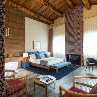 Ispirazione per una camera matrimoniale mediterranea con parquet scuro, pareti marroni, camino classico, cornice del camino piastrellata e pavimento marrone