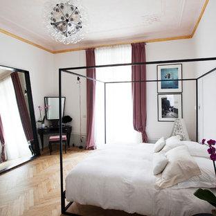 Foto di una camera da letto minimal con pareti bianche, pavimento in legno massello medio e nessun camino