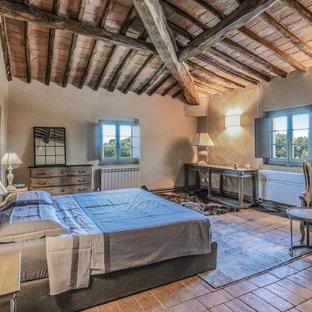 Imagen de dormitorio principal, de estilo de casa de campo, grande, con paredes beige, suelo de ladrillo y suelo naranja
