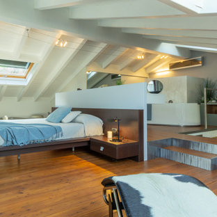 Photo of an expansive contemporary loft-style bedroom in Other with blue walls, painted wood floors and brown floor.