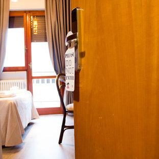 Modelo de dormitorio principal, actual, de tamaño medio, con suelo laminado y suelo beige
