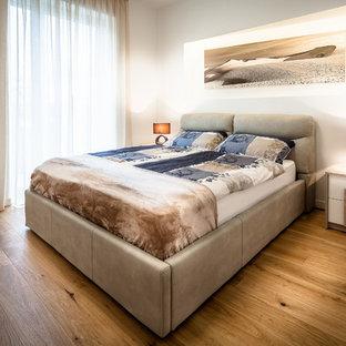 Idee per una camera matrimoniale contemporanea con pareti bianche e pavimento in legno massello medio