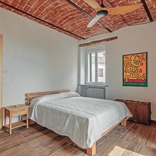 Immagine di una camera da letto mediterranea con pareti bianche e pavimento marrone