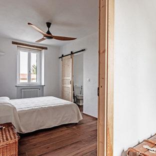 Ispirazione per una camera da letto mediterranea con pareti bianche e pavimento marrone