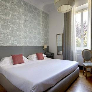 Esempio di una camera degli ospiti minimalista di medie dimensioni con pareti grigie, pavimento in legno verniciato e pavimento marrone