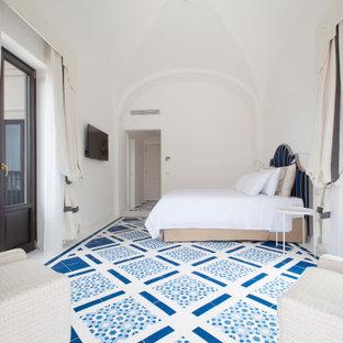 Immagine di una camera da letto mediterranea con pareti bianche e pavimento blu