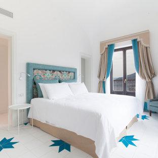 Foto di una camera da letto mediterranea con pareti bianche e pavimento multicolore