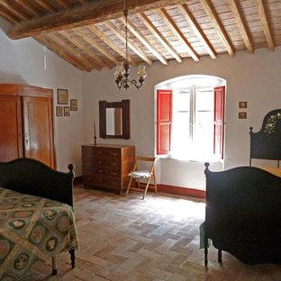 Ejemplo de dormitorio principal, de estilo de casa de campo, de tamaño medio, con paredes blancas, suelo de ladrillo y suelo rojo