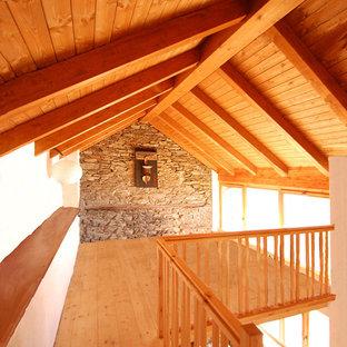 Ejemplo de dormitorio tipo loft, rural, de tamaño medio, con paredes blancas, suelo de madera clara y suelo naranja