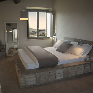Photo of a mid-sized scandinavian guest bedroom in Bologna with beige walls and terra-cotta floors.